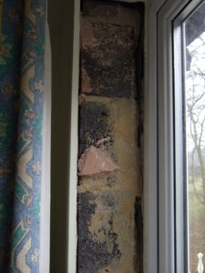 "The plasterboard fully removed from a window reveal, note the presence of thermal bridging made worse by the use of bricks. Also note that there are lots of gaps between the masonry and the vertical dpc, these draughts could blow behind the reveal lining and on round the corner and behind the wall lining boards. Hence the expression ""like living in a plasterboard tent""."