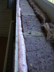 The top of the plasterboard below a window board filled with foam.