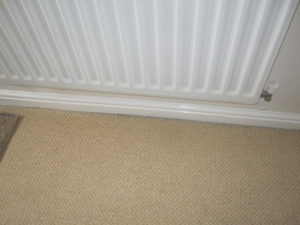 Note darkening to the edge of the carpet due to dust and dirt from outside brought in by draughts, in this case through a beam and block ground floor.